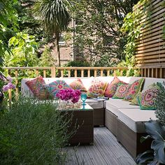 Garden terrace.  In the summer months, this garden terrace is used as an extension of the house. Swap traditional recliners for a large garden seating area. This decking has been warmed up with clever planting and colourful cushions — perfect for a relaxed evening with friends.