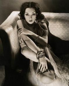 Mexican actress Lupe Velez with very dark hair parted in the center sitting in the corner of a couch with her legs on the couch embracing herself... - Vanity Fair 1932
