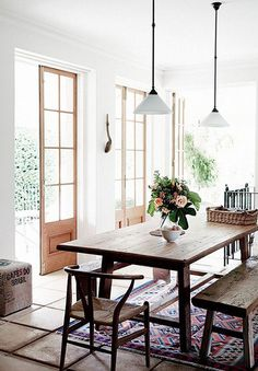 The kilim rug in this dining room ties the whole space together. Fresh flowers are always a good idea.