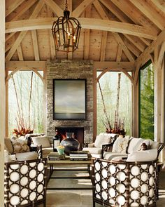 This country home features a screened-in porch with a fireplace.