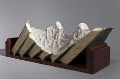 Mountain sculptures from discarded books: Carving into the discarded stacks of books, he has created fantastic, romantic landscapes which remind us that though our fascinations and the value we put on different ideas have changed, we as a species have not evolved that much.