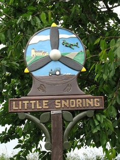 Village sign by Evelyn Simak, via Geograph Little Snoring