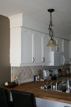 Quick fix...paint your bulkheads to match your ceiling and add crown moulding!  Check out before and after pics!