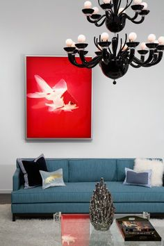 "I really love the color of this sofa paired with the black chandelier. The red photograph of the light-box mounted fish is called ""Orson Welles"" and is by artist Dirk Westphal."