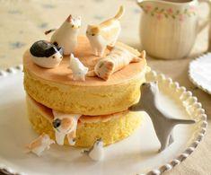 Những chú mèo tinh nghịch đang chơi trốn tìm quanh chiếc bánh ngọt vàng ươm.