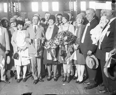 SUMMARY Full-length portrait of Lois Delander, Miss America 1927, holding a bouquet of flowers, standing with a large group of people in a room in Chicago, Illinois. Delander is wearing a sash, and a man and woman standing next to her are both holding trophies. Men standing in the foreground are wearing light-colored ribbons on their jackets.