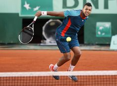 France's Jo-Wilfried Tsonga hits a return to Switzerland's Stanislas Wawrinka during their Men's Singles 4th Round tennis match of the French Open tennis tournament at the Roland Garros stadium, on June 3, 2012 in Paris.