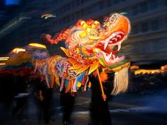 Chinatown dragon float, San Francisco | A line of men carry a colorful dragon float during the famous Chinese New Year Parade through Chinatown