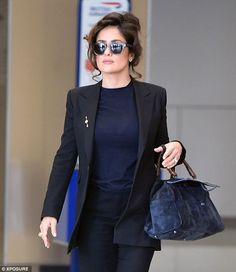 Shady lady: She wore dark sunglasses for the occasion which gave her look a superstar edge...
