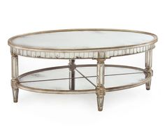 """21""""Hx51""""Wx32""""D Keswick Oval Cocktail Table. The Parisian silver finish of this detailed table sets off the antique hand aged mirrors. The rim has over 80 small mirrors, below which there is a quartered mirror undershelf."""