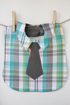 Your little guy will stand out from the mainstream in this teal and grey plaid dress shirt style bib complete with collar and appliqued grey tie. Back lining matches the tie for a reversible effect. Perfect for * dressing up your little man at your next dinner out * using as a