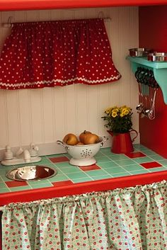 """Play kitchen made from old entertainment center.  Love the """"tile"""" counter top and bead board back splash.  Cute little turquoise shelf with hooks for utensils!"""
