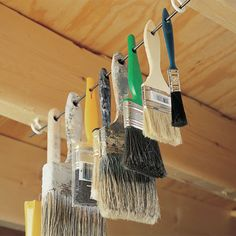 Out-of-the-way paintbrush storage  Hang brushes on a rod or wire  1 of 1  Hang brushes on a rod or wire    Hang your paintbrushes out of harm's way by installing a couple of screw eyes or cup hooks on the bottom of a couple of rafters or floor joists. Then thread the brush handles through a stiff wire (or welding rod) and hang it all up.