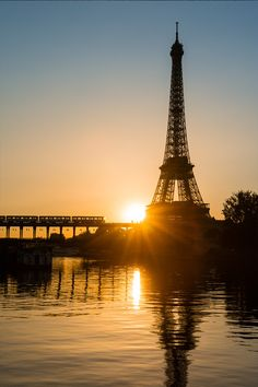 The setting sun silhouettes the Eiffel Tower and Metro Line 6 in Paris // photo by @justinfoulkes #paris #eiffel #sunset