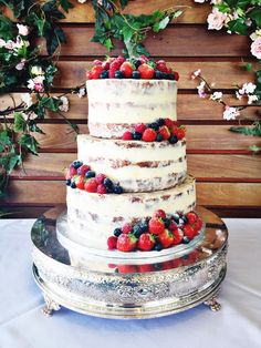 Semi-naked wedding cake with fresh berries and dusting of powedered sugar