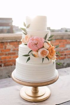Four tiered buttercream cake with fresh peach and pink flowers