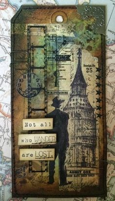 Altered & Inked: Tag Base: Manila Tag Stamps: Viva Las Vegas Stamps: Businessman Silhouette Big Ben Waybill/Invoice background Not all who wander Embellishments: Tim Holtz: Remnant Rubs, Filmstrip ribbon, mini paper clips, metal corner, tissue tape. Inks and Powders: Distress Ink , Archival - Jet Black. Distress Embossing powder - Walnut stain Machine Stitching and cotton.