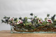 <p> An arrangement in a glass planter was made with four ingredients—Picasso lilies, lavender scabiosa, and Blue Thistle in a...