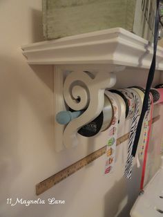 wooden curtain rod through bookshelf corbel to create ribbon storage - how clever! :)