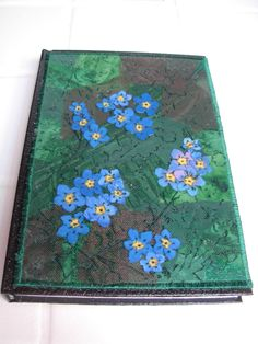 Forget-me-nots created with a soldering iron mounted on a sketchbook.