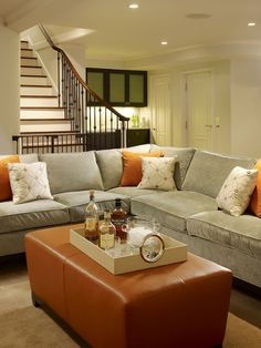 Cozy, chic blue gray tobacco basement living space design! Gray velvet sectional sofa, range silk pillows and orange leather ottoman.