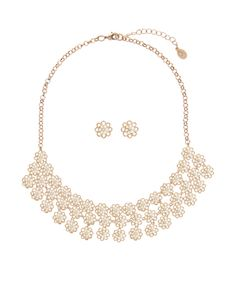 This pretty collar necklace is adorned with cascading, cut-out daisies with small crystal gem studs, and also features a pair of matching earrings. Please be aware that this item is non-refundable. Matching items available.