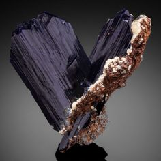 AZURITE Touissit, Touissit District, Jerada Province, Oriental Region, Morocco Intense deep navy blue Azurite crystal with glassy luster rising from another partial crystal that has remnants of the wall rock. Azurite has saw edge multiple termination