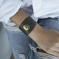 Courtesy #bracelet This statement #leather #cuff is the perfect expression for someone who loves a compliment. Soft buttery leather, polished metal with a luminous center stone. Measurement: Fits up to a 7″ wrist Materials: grey leather with polished brass and an #aqua stone black leather with polished brass and a #slate stone Leather Cuffs, Grey Leather, Slate Stone, Polished Brass, Wood Watch, Compliments, Aqua, Metal, Bracelets