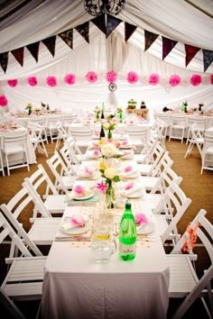bottles used as a vased centerpiece with flowers around the napkins and pom-poms hanging down.