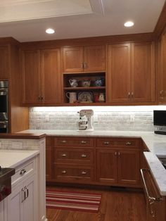 natural cherry cabinets, carrara marble counters, polished nickel hardware. Country kitchen.