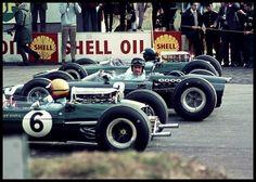 Graham Hill se retourne avant le départ, encadré par 2 pilotes Lotus. A cette époque ils étaient 3 sur la même ligne.