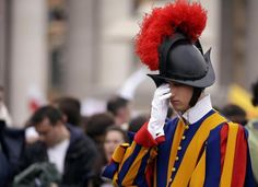 A Swiss guard touches his face as Pope Francis leads a solemn ceremony in St. Peter's Square at the Vatican Sunday, April 2014 Swiss Guard, Military Figures, City Landscape, The Hundreds, Riding Helmets, Rome, Winter Hats, April 27, Pope Francis