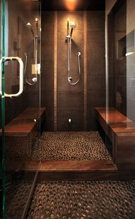 I LOVE THIS.  The fusion of natural tone granite on twin bench seating and shower threshold mimick an exotic hardwood and  the river rock shower floor evokes images of a stone creek bed.  The dark tile contrased with lighter vertical tiles complement the the bilateral balance of the seating and recessed shower lighting tops it off to create a dramatic setting.