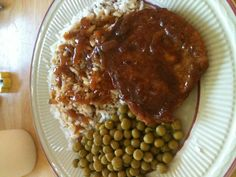 Smothered pork chop with rice & gravy and peas.