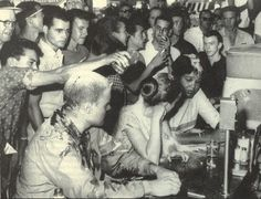 Sit-in at the Woolworths lunch counter in Jackson, Mississippi, 1963.  Annie Moody (far right) was a student at Tougaloo College in Jackson. Mustard and ketchup drip off her forehead. Joan Trumpauer (center), a white student at Tougaloo, had been doused with mustard, ketchup, water, Coca-Cola, and spray paint.  Tougaloo professor John Salter (left) is covered in condiments and blood.  He had been hit with brass knuckles.