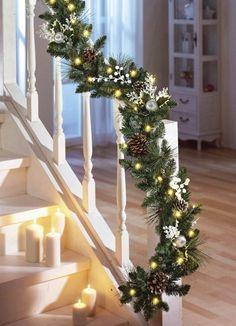 une guirlande artificielle de sapin décorée de pommes de pin et branchettes blanches