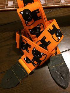 Cool guitar strap -- cute black cartoon cats on an orange background by MyMumDrivesaUFO on Etsy