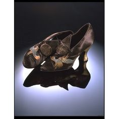 This evening shoe is made of brown satin, with a hand-painted bird motif in tones of blue and gold. The heel is of medium height and is painted in gold. Made by Stead & Simpson London 1922