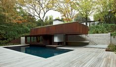 House on Ravine Edge Shim-Sutcliffe Architects Toronto A board-formed-concrete retaining wall and stair lead to the pool house.