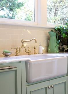 Cabinets in sea-foam green anchor a deep farmhouse sink with Victorian-style brass faucet.