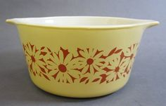 with applied pale yellow color and applied orange decal; machine made. Circular shaped white dish with handles and pale yellow exterior, decorated with orange daises. 1 l / PYREX Vintage Crockery, Vintage Pyrex, Vintage China, Vintage Kitchen, Corelle Ware, Retro Kitchen Accessories, Corning Museum Of Glass, White Dishes, Milk Glass