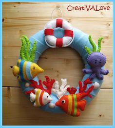 Un salvagente, un polpo, pesci e coralli decorano la ghirlanda a tema marino. Una creazione in feltro/pannolenci. Handmade Felt Creations.