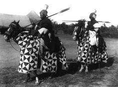 Men on horseback Cameroons 1931-32. Cam II. Binoc XI.15. Men On Horseback.This image looks contradictory. Africans on horseback, looking very like Mediaeval European. Perhaps a good example of intercultural influence.