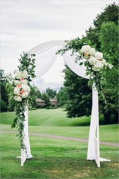 Romantic arched arbour, draped with white chiffon and accented with white and peach flowers and greenery.