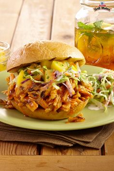 Fork-tender pulled chicken in a homemade barbecue sauce is piled onto a fresh roll and topped with an awesome peach salsa. These tasty chicken sliders are perfect for your next summer cookout.