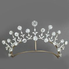 A delicate diamond tiara, 1905, made for a 'piled high hairstyle'. Featuring fifteen diamond pinnacles and smaller spacers, each topped with a circular diamond, with nine circular diamonds at the base of each pinnacle.