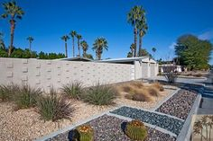 Palm Springs area landscaping. Varying, contained rock beds and repetition of plants make a stylish front area