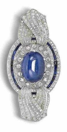 A sapphire, synthetic sapphire and diamond brooch, circa 1915. The oval cabochon sapphire within a pierced oval surround with twisted ribbon finials, millegrain-set throughout with single and rose-cut diamonds and accented with a row of calibré-cut synthetic sapphires,  single-cut diamonds approximately 4.00 carats total, width 7.0cm. #BelleEpoque #brooch