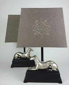 Pair of Resin Greyhounds in Gold Finish Posing 	on Black Plinth with Taupe Silk and Linen Shade 	 	Base: 12.5