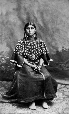 Studio portrait (sitting) of Julia Gerry, a Native American (Shoshone) woman. She wears moccasins, a dress decorated with elk teeth, a leather belt decorated with metal, and bead necklaces with bead and medal pendants. Native American Clothing, Native American Photos, Native American Women, Native American History, Native American Indians, Cheyenne Indians, Costume Ethnique, Native Indian, Indian Tribes